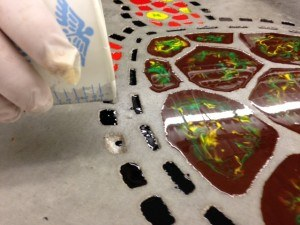 Adding epoxy to the engraved decorative concrete mosaic turtle.